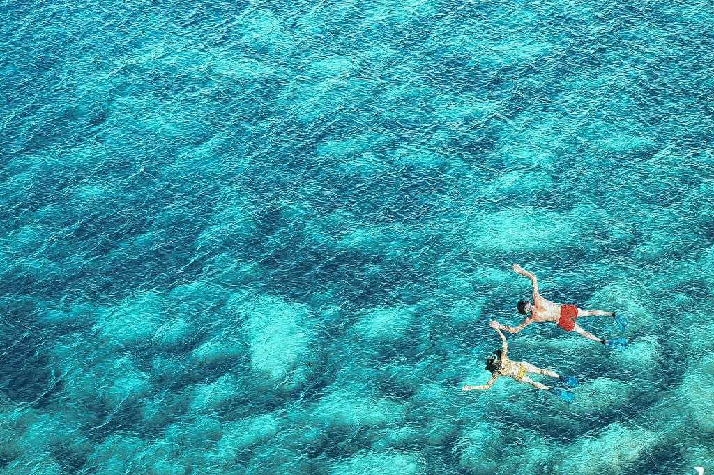 Above view of couple snorkeling in blue sea water. Summer vacation concept